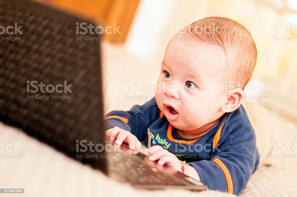 Four months baby with laptop stock photo