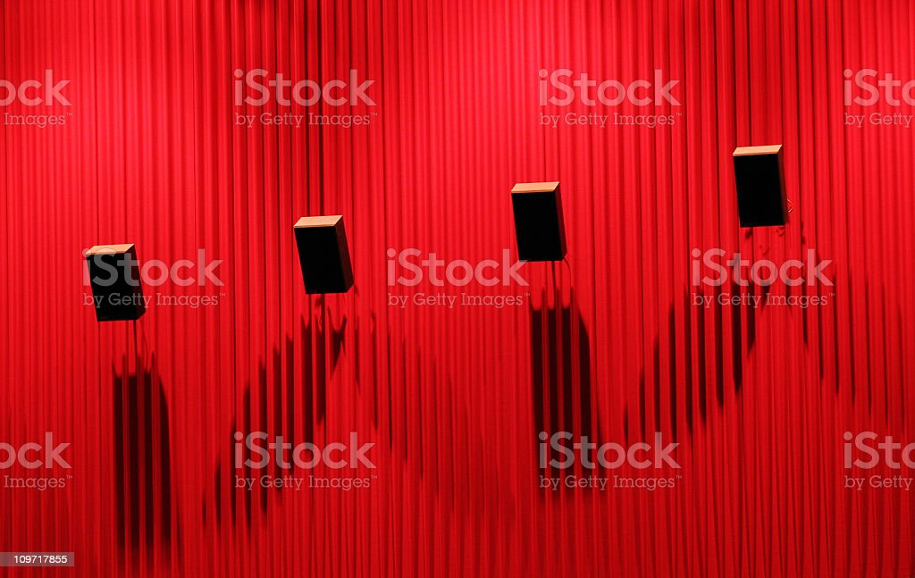 Four Movie Theater Speakers on Red Wall stock photo