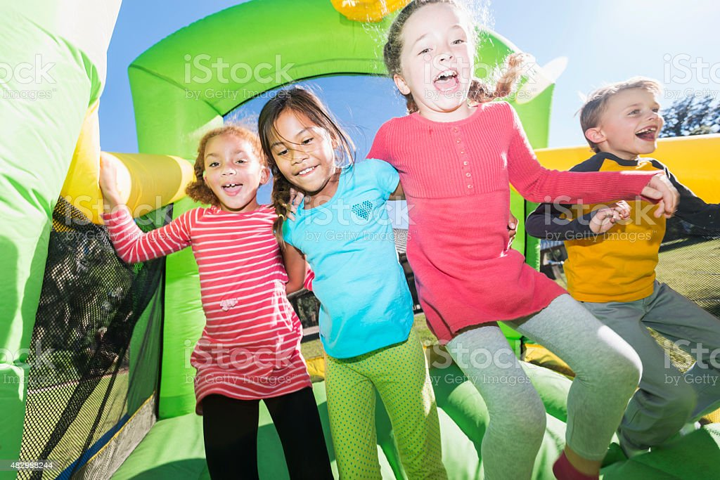 Four multi-ethnic children jumping on bouncy castle stock photo
