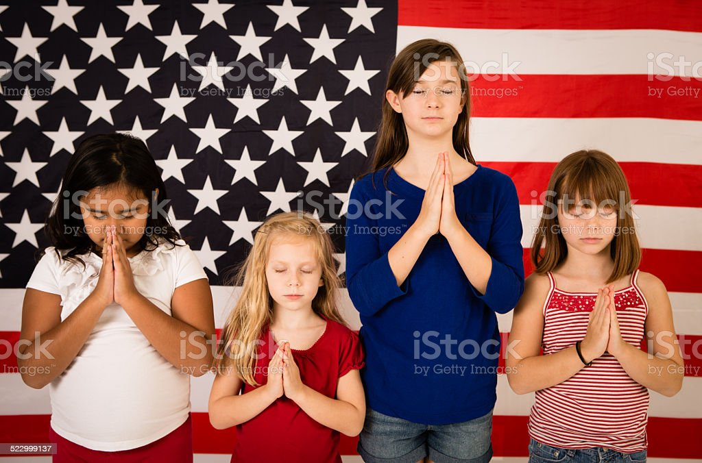 Four Multi-Ethnic Girls Praying in Front of American Flag stock photo