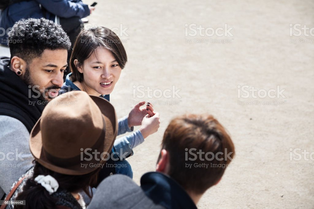 four multi-ethnic young friends chat  in spring sunshine in Paris stock photo