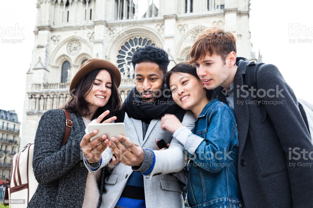 four multi-ethnic young friends have fun posing for selfies  in spring sunshine together by Notre Dame in Paris stock photo