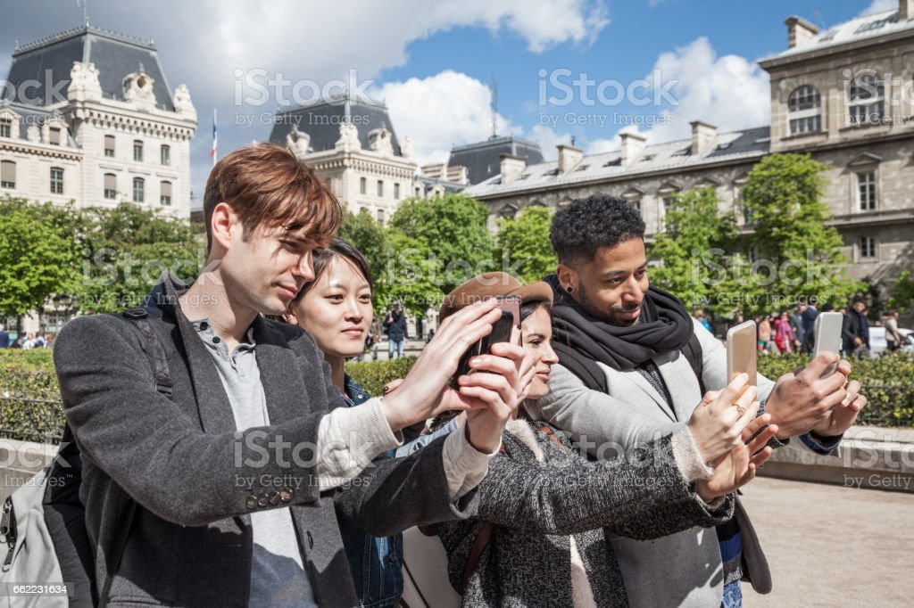 four multi-ethnic young friends have fun posing for selfies  in spring sunshine together near Notre Dame in Paris stock photo