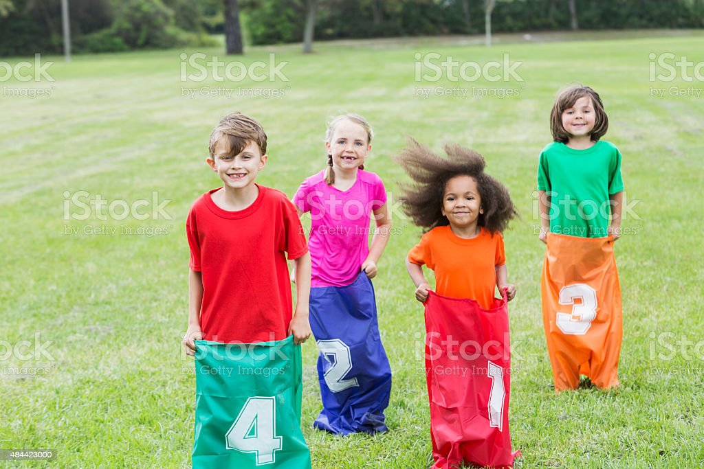 Four multiracial children in potato sack race stock photo