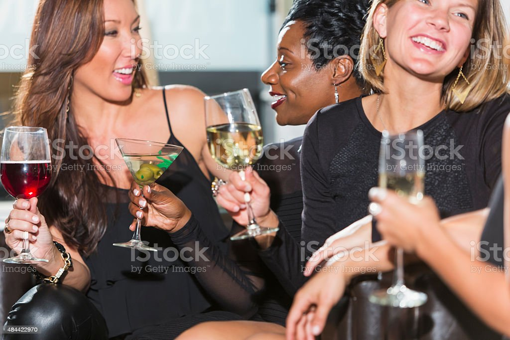 Four multiracial women at a party talking and drinking stock photo