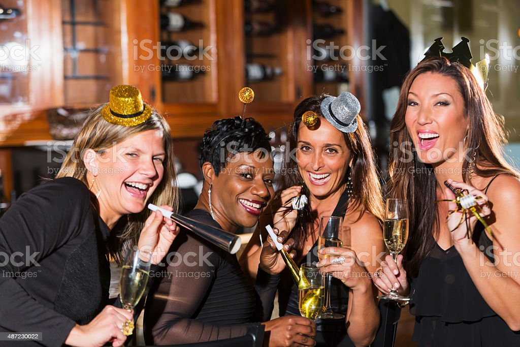Four multiracial women at a party with champagne stock photo