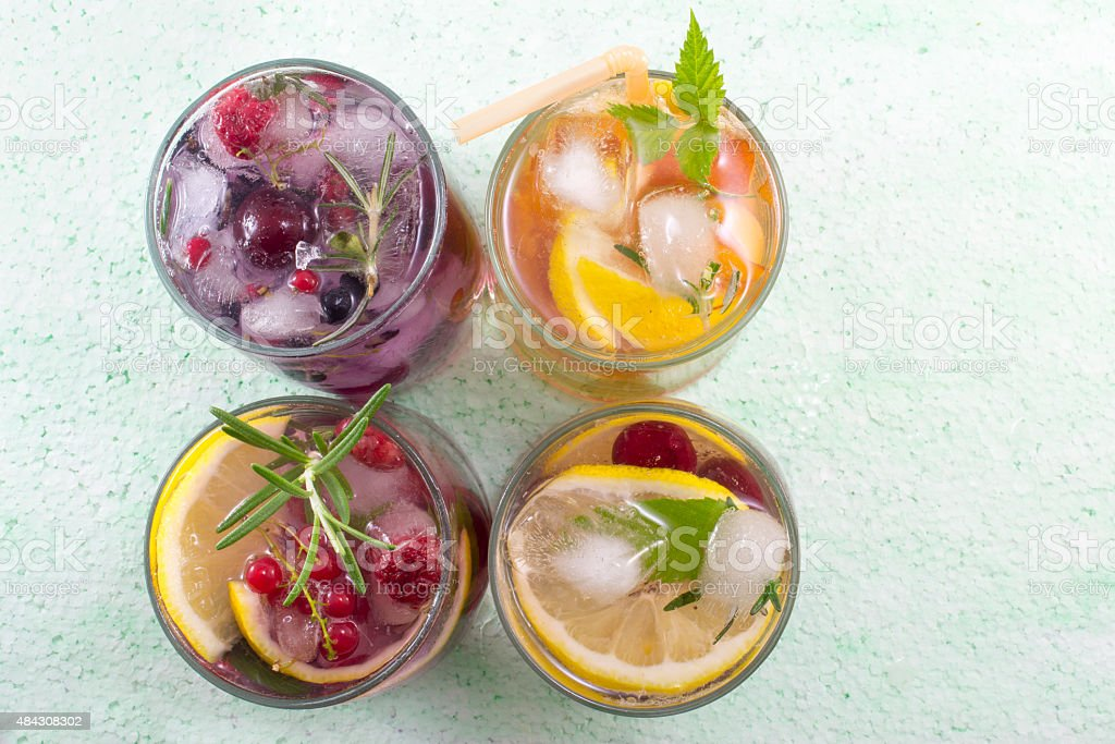 Four non alcoholic fruit cocktails arranged on the green table stock photo