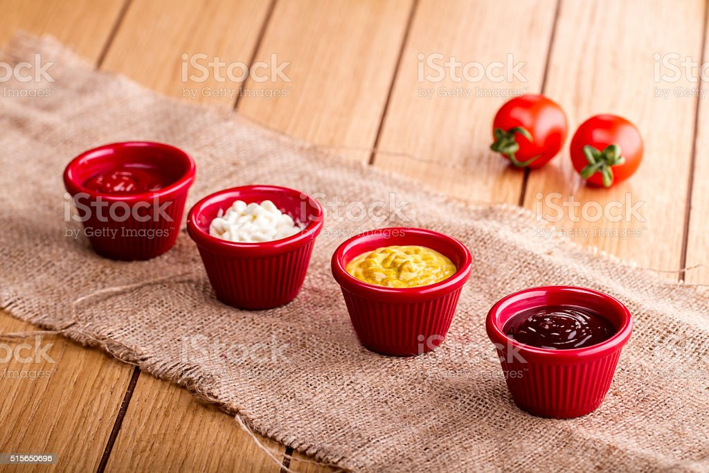 four of various sauces on wood table stock photo