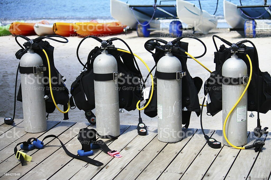 Four oxygen tanks lined up on the boardwalk for scuba diving stock photo