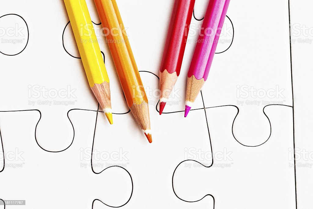 Four pencil crayons ready to create jigsaw design on blank royalty-free stock photo