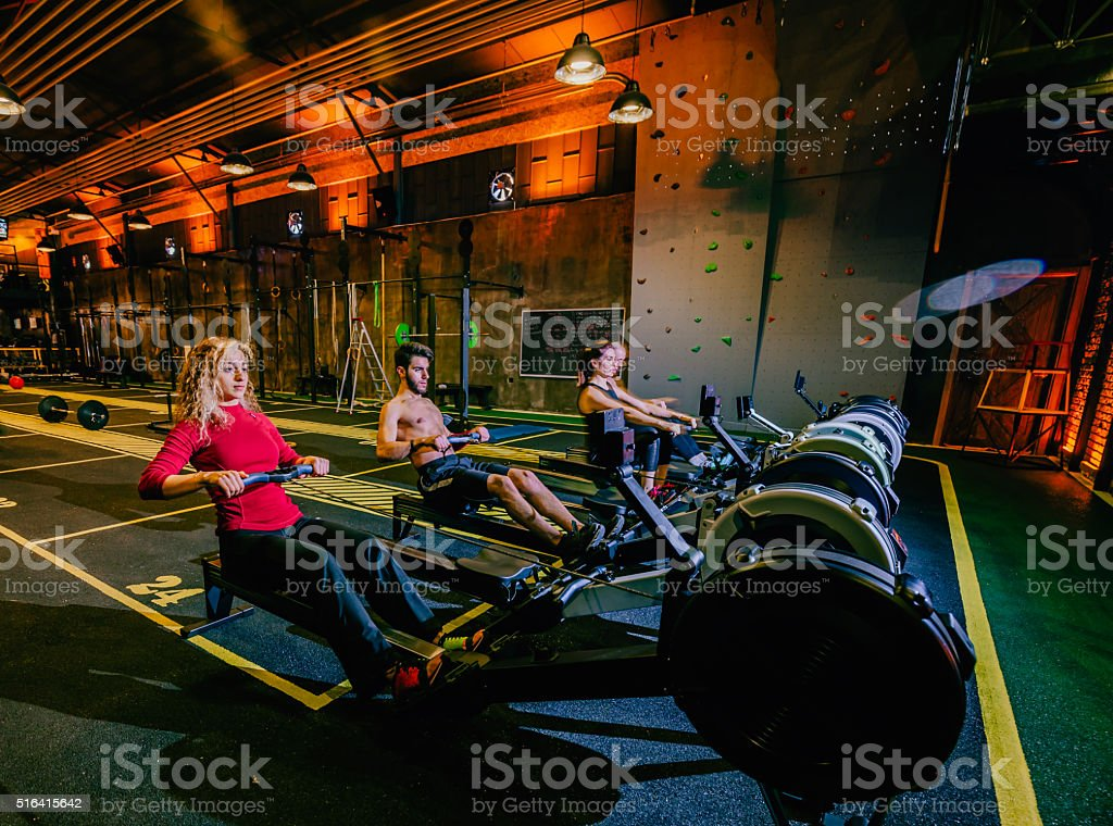 Four people  at a gym on rower machine stock photo