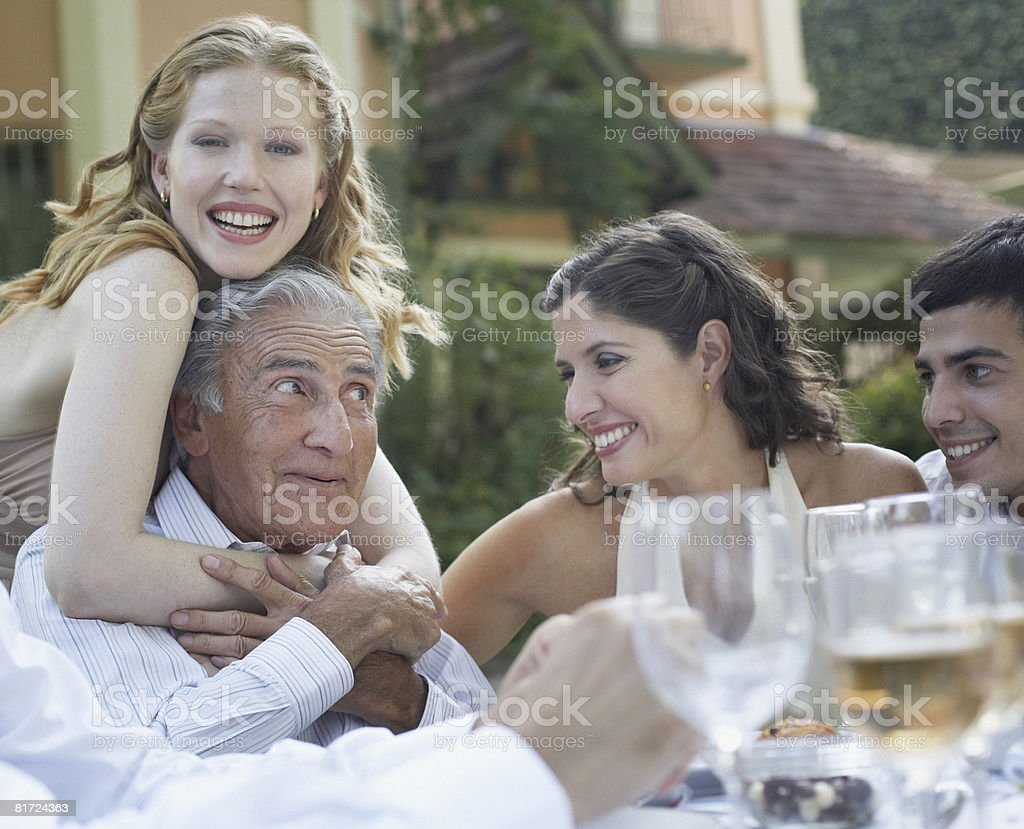 Four people at outdoor party smiling and being affectionate royalty-free stock photo