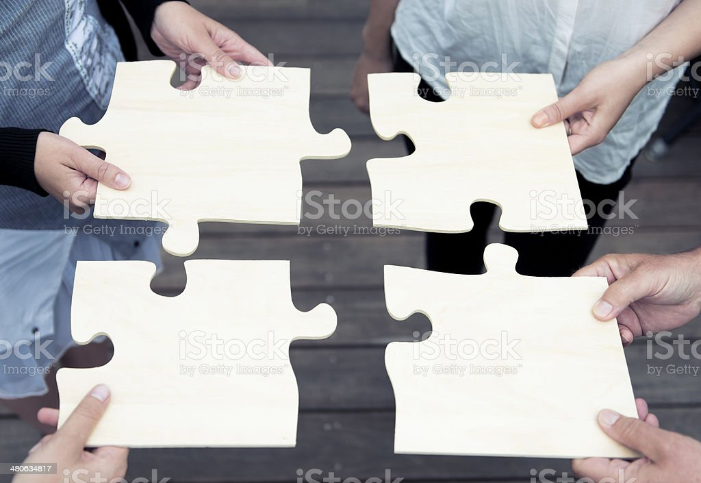 Four people complete a large jigsaw puzzle royalty-free stock photo