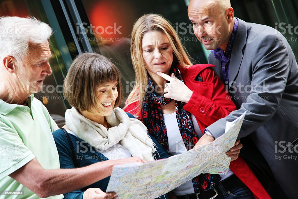 Four People Discussing Map royalty-free stock photo