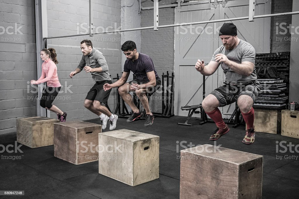 Four people doing box jumps in cross training class stock photo