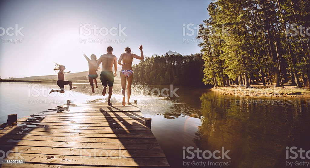 Four people jumping off a jetty into the water stock photo