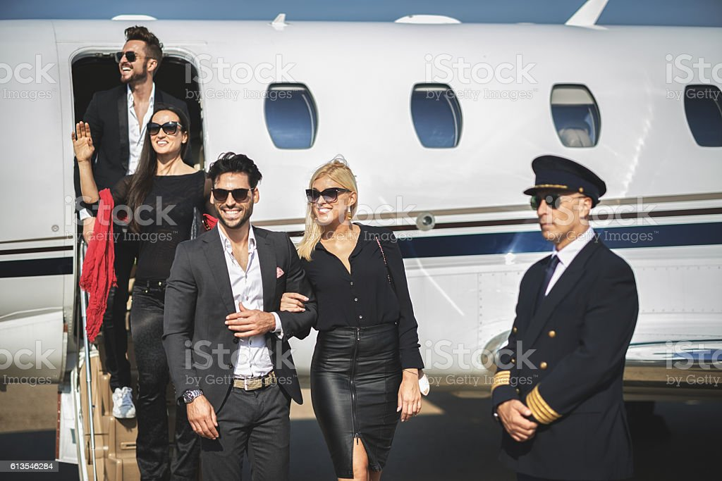 Four people leaving private jet airplane stock photo