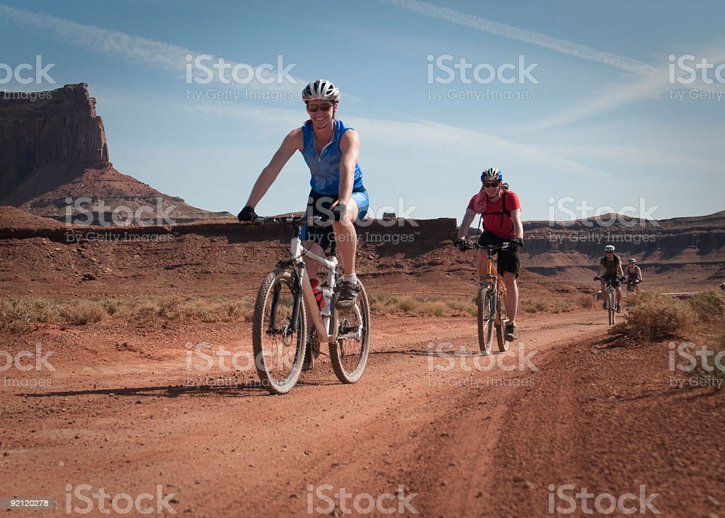 Four people mountain biking in the desert. stock photo
