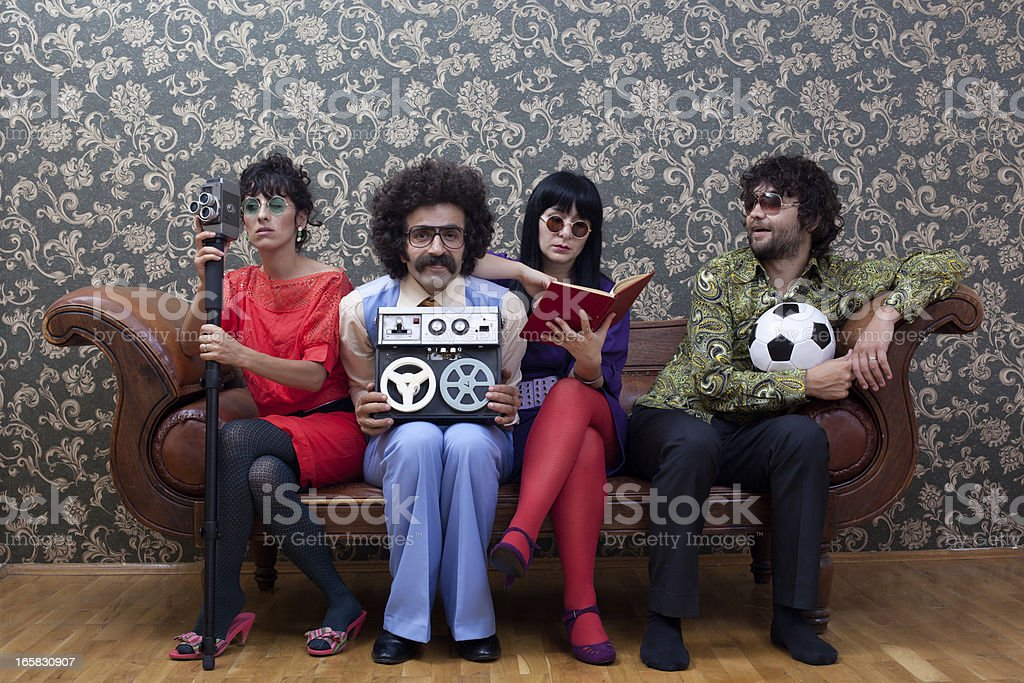 Four people sitting on sofa each has different hobby royalty-free stock photo