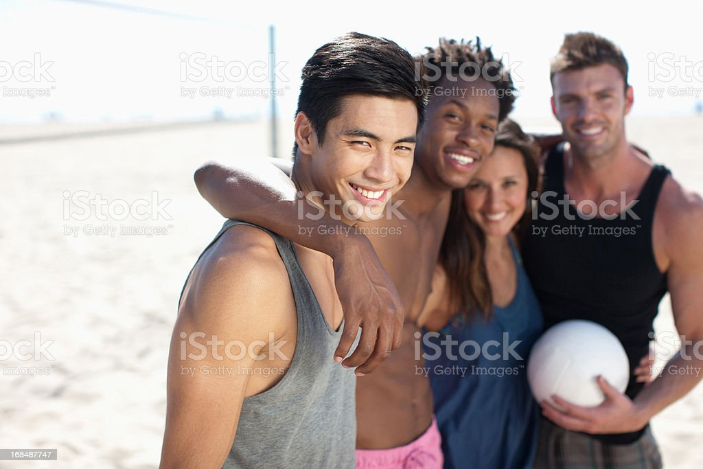 Four people standing on beach volleyball court royalty-free stock photo