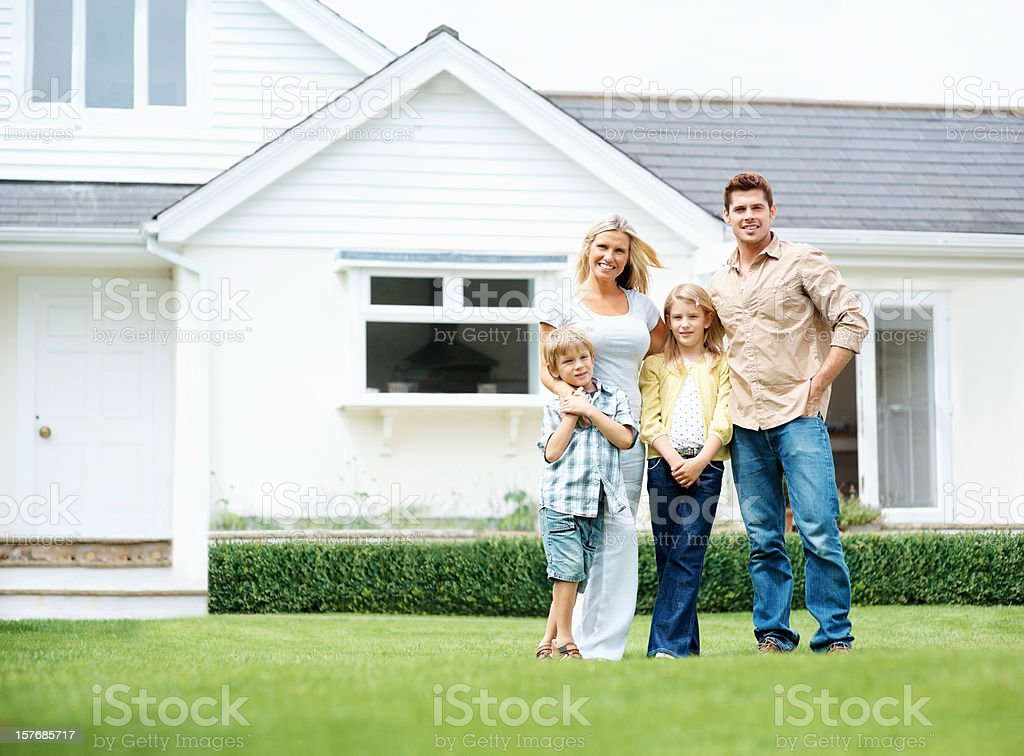 four people standing on lawn in front of their house stock photo