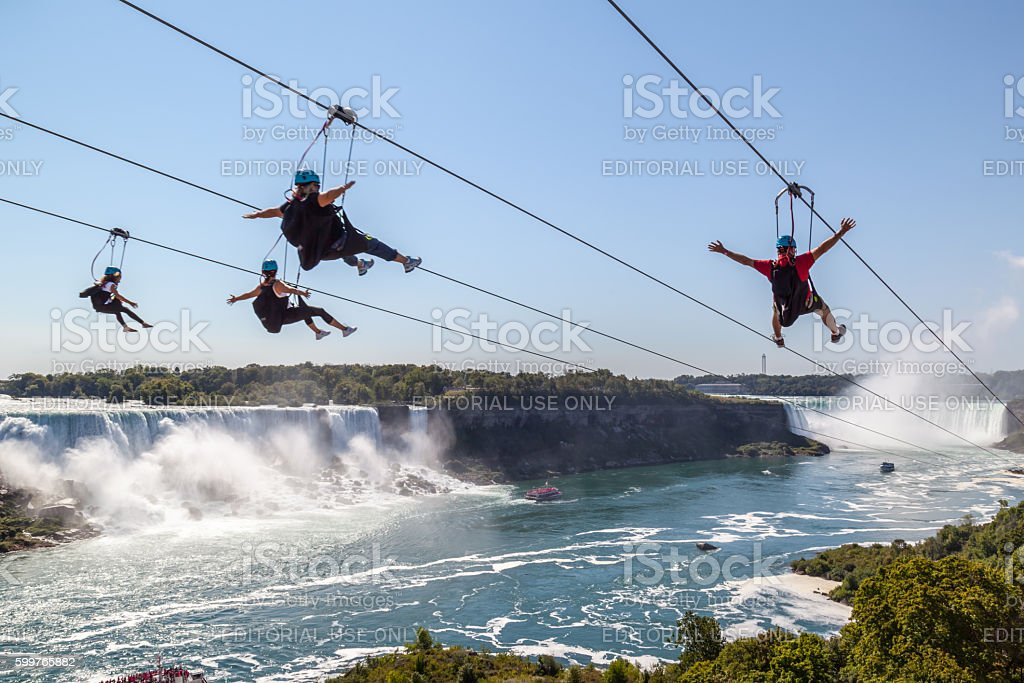 Four people taking zipline ride at Niagara Falls, Ontario, Canada. stock photo