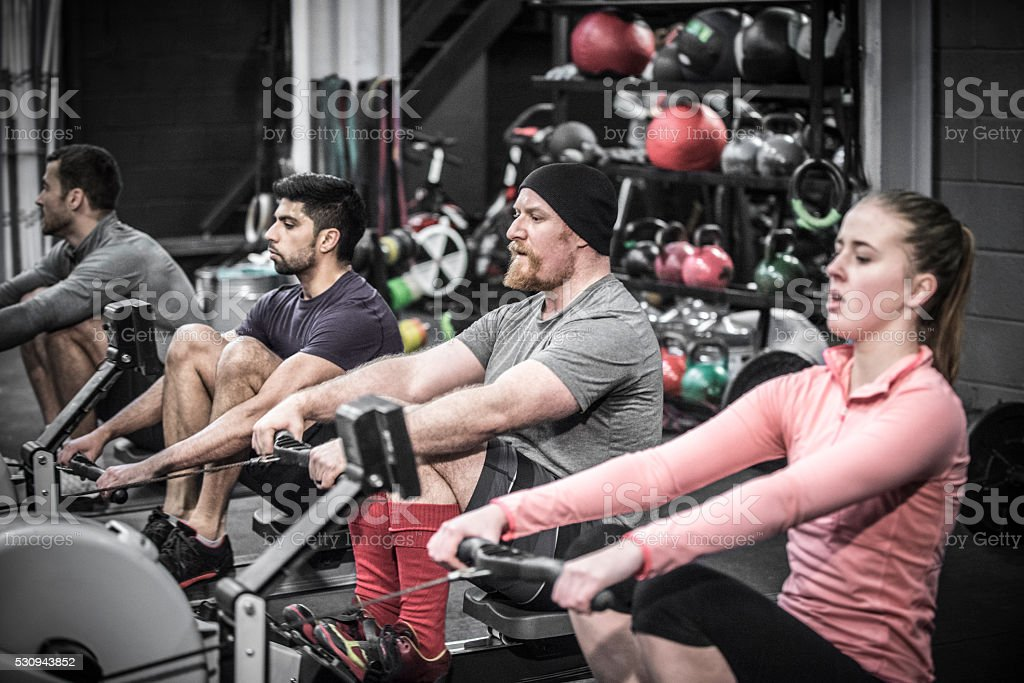 Four people using rowing machines in cross training class. stock photo