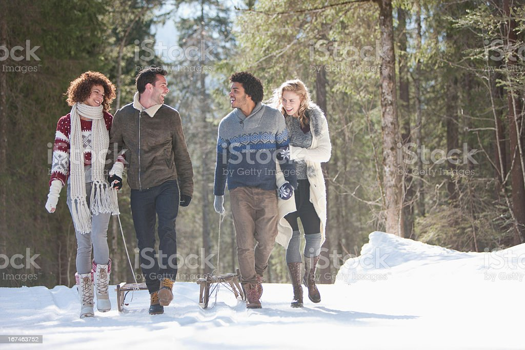 Four people with sled in snowy landscape stock photo