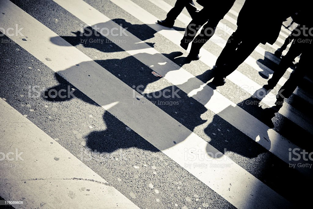 Four people's shadows casted across a walkway royalty-free stock photo