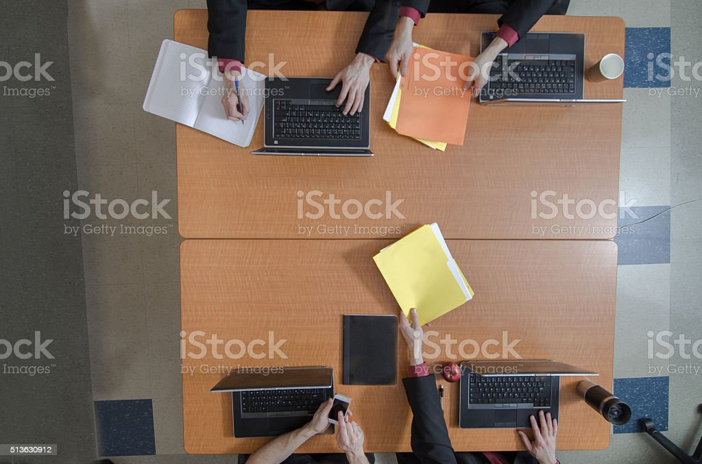 Four persons meeting at a table seen from above stock photo