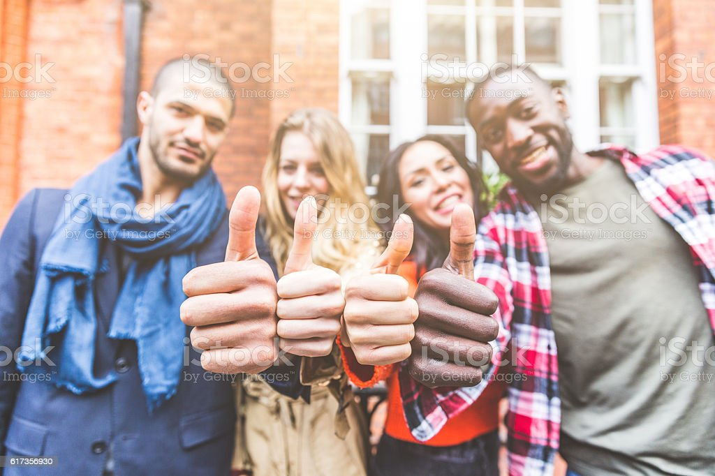 Four persons with different ethnicities showing thumbs up stock photo