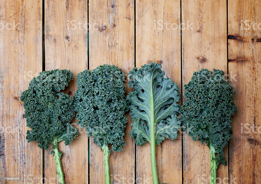 Four pieces of kale one turned over on a wooden background stock photo