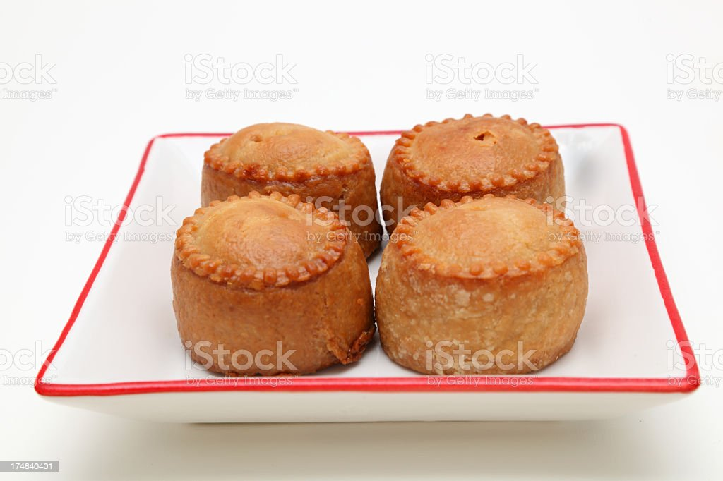 four pork pies on white plate with plain background stock photo