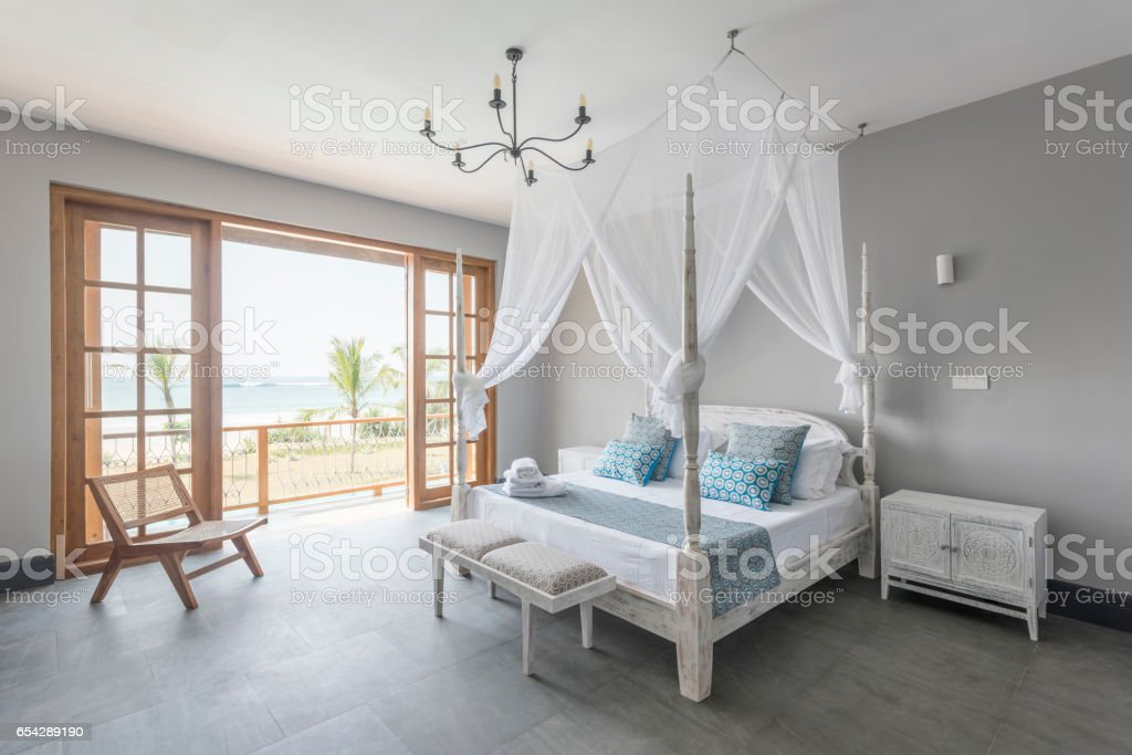 Four poster bed with mosquito net in bright hotel room stock photo
