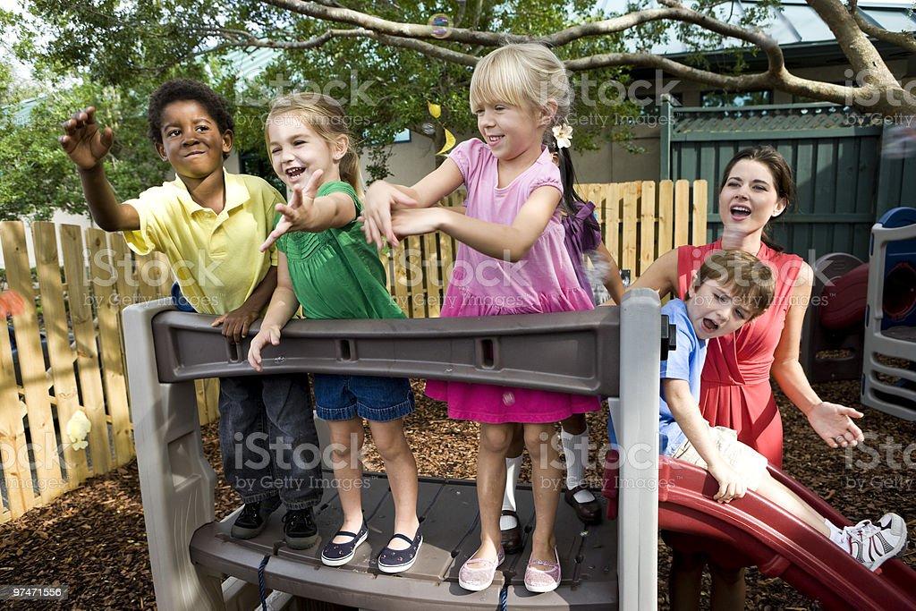 Diversidad de preescolar niños jugando en el patio de juegos con profesor de cuidados diurnos para foto de stock libre de derechos