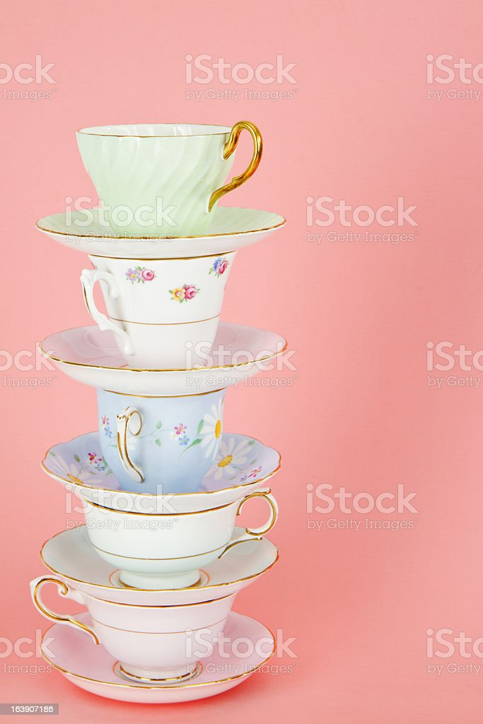 Four Pretty Old Fashioned Antique Teacups Stacked On Pink stock photo