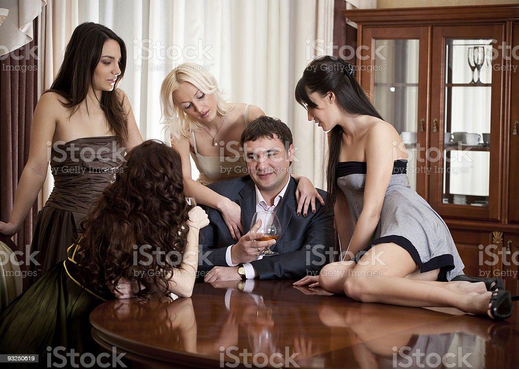 Four pretty women seduce à one man in a room stock photo