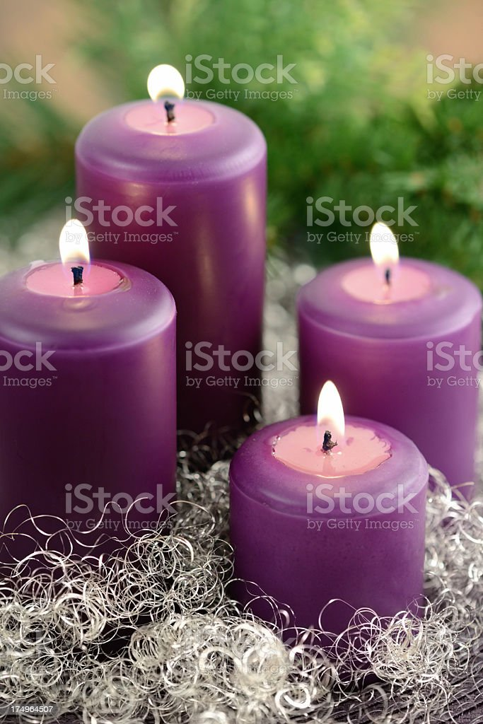 four purple Advent candle burning with wreath and silver decoration royalty-free stock photo