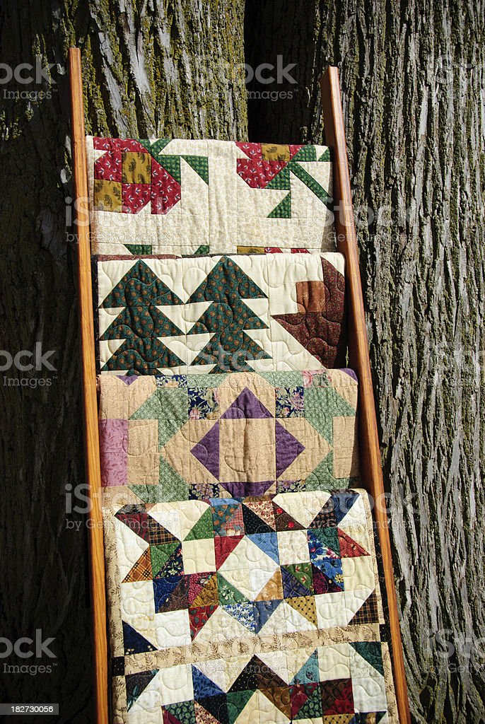 Four quilts on a quilt rack royalty-free stock photo