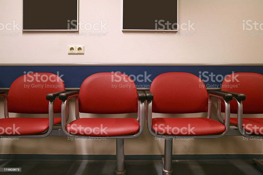 Four red chairs in a waiting room with blank paintings royalty-free stock photo