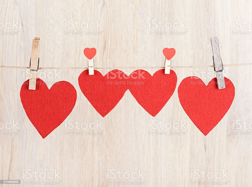 Four red hearts hung on the rope stock photo