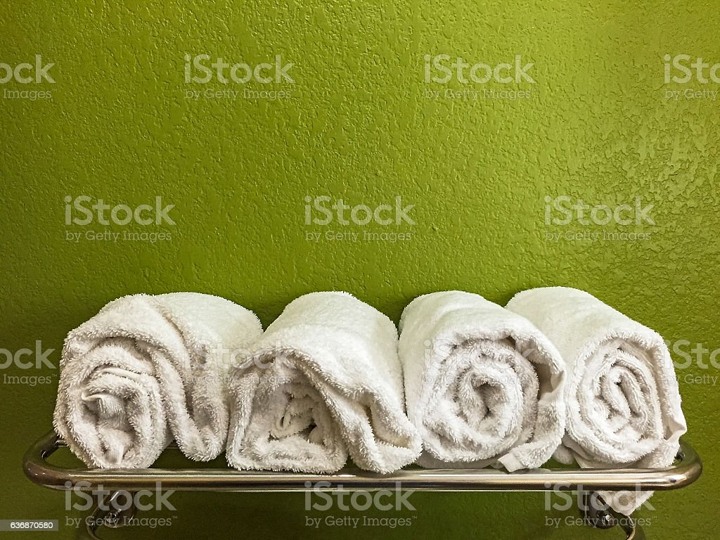 Four rolled white bath towels on shelf with green wall stock photo