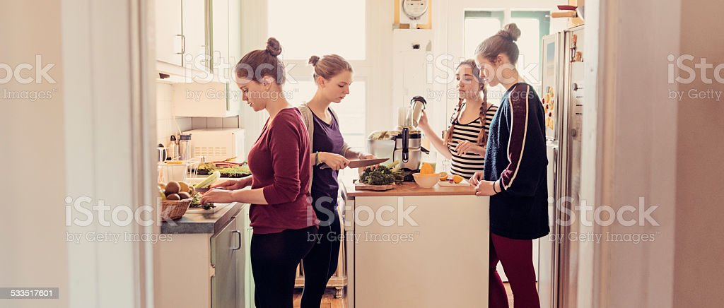 Four roommates using a juicer in their appartement kitchen. stock photo