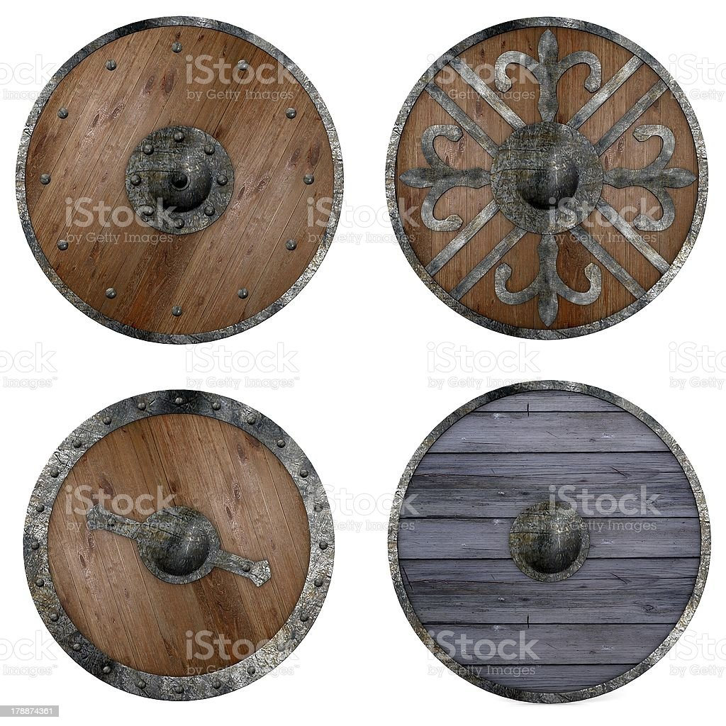 Four round wooden shields with assorted metal decorations stock photo
