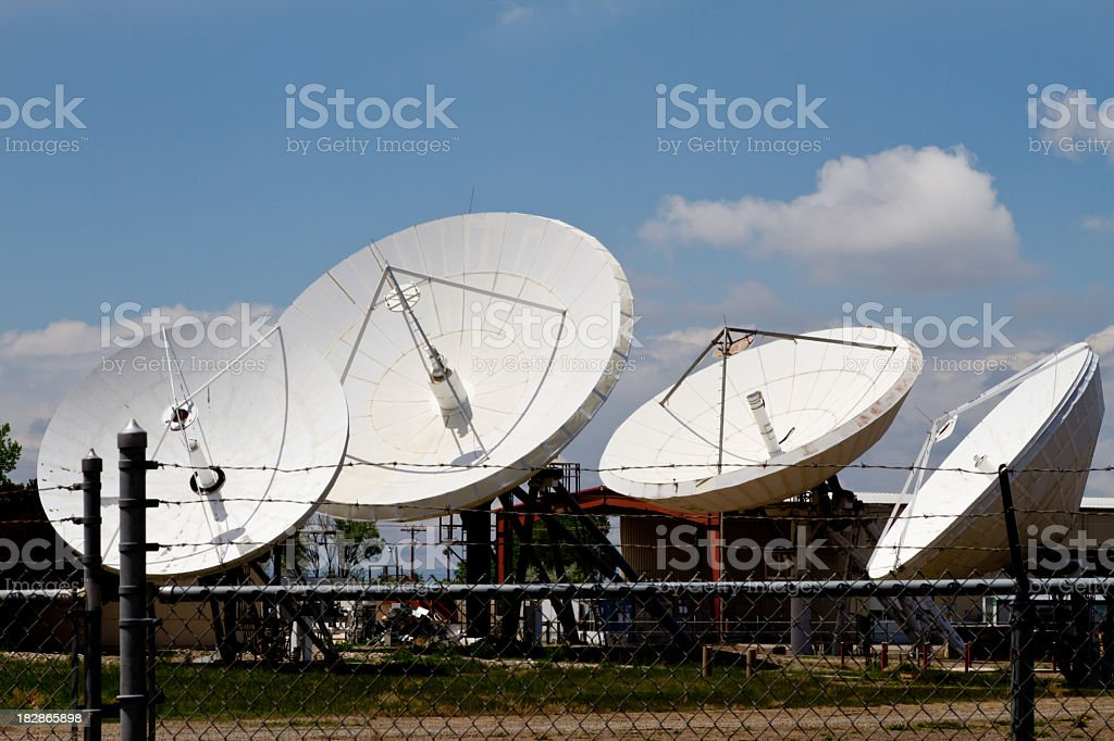 Four Satellite Dishes Behind Barbed Wire royalty-free stock photo