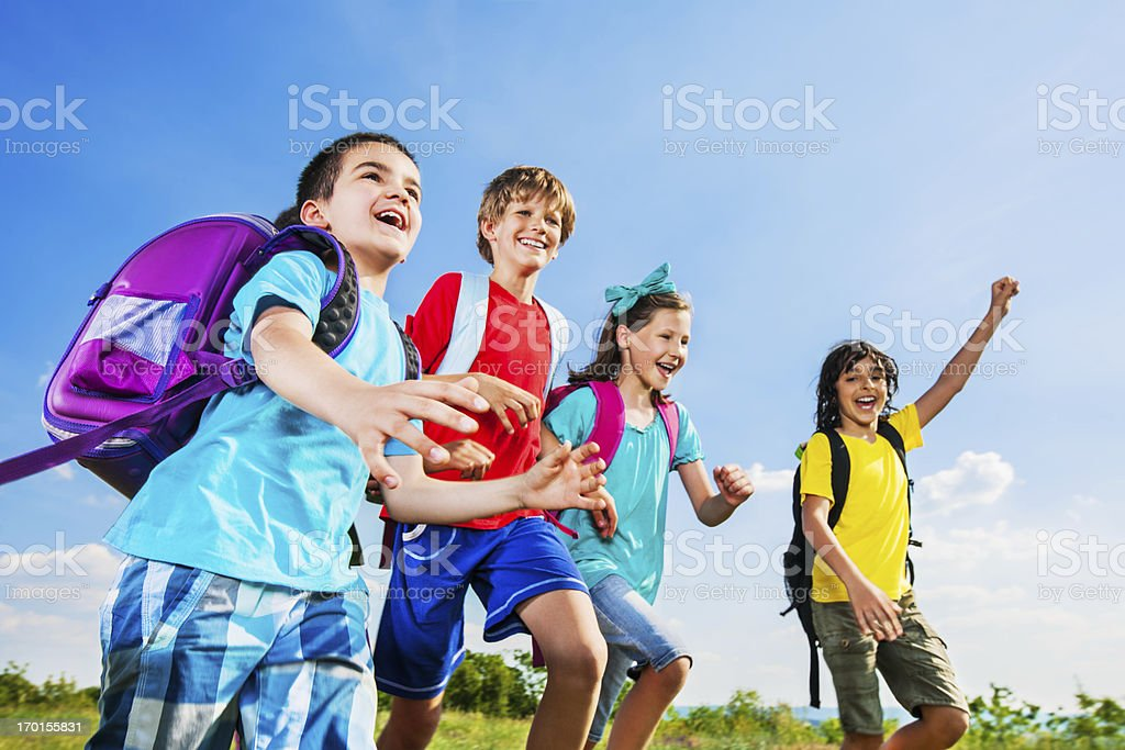 Four school children running in the nature. royalty-free stock photo