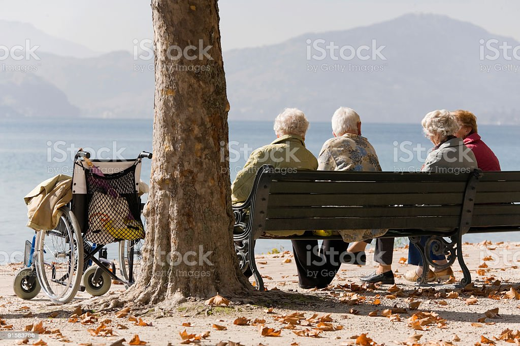 Four senior women with wheelchair sitting lakeside in sunlight (XL) royalty-free stock photo