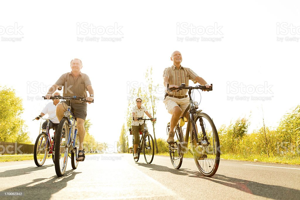 four seniors biking on road royalty-free stock photo