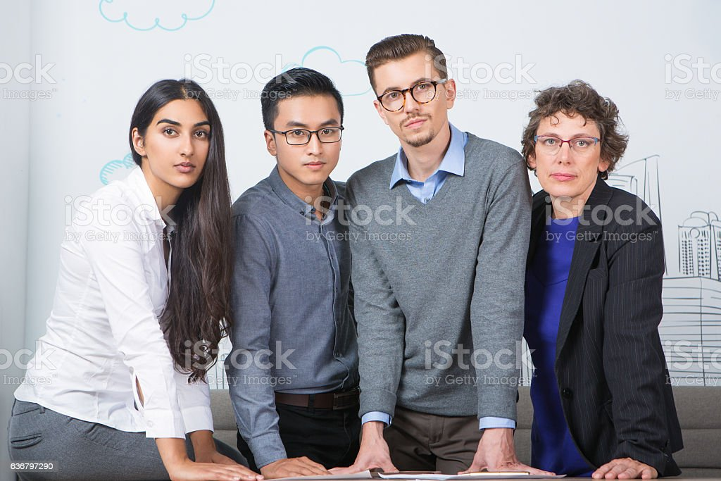 Four Serious Business People Standing at Table stock photo