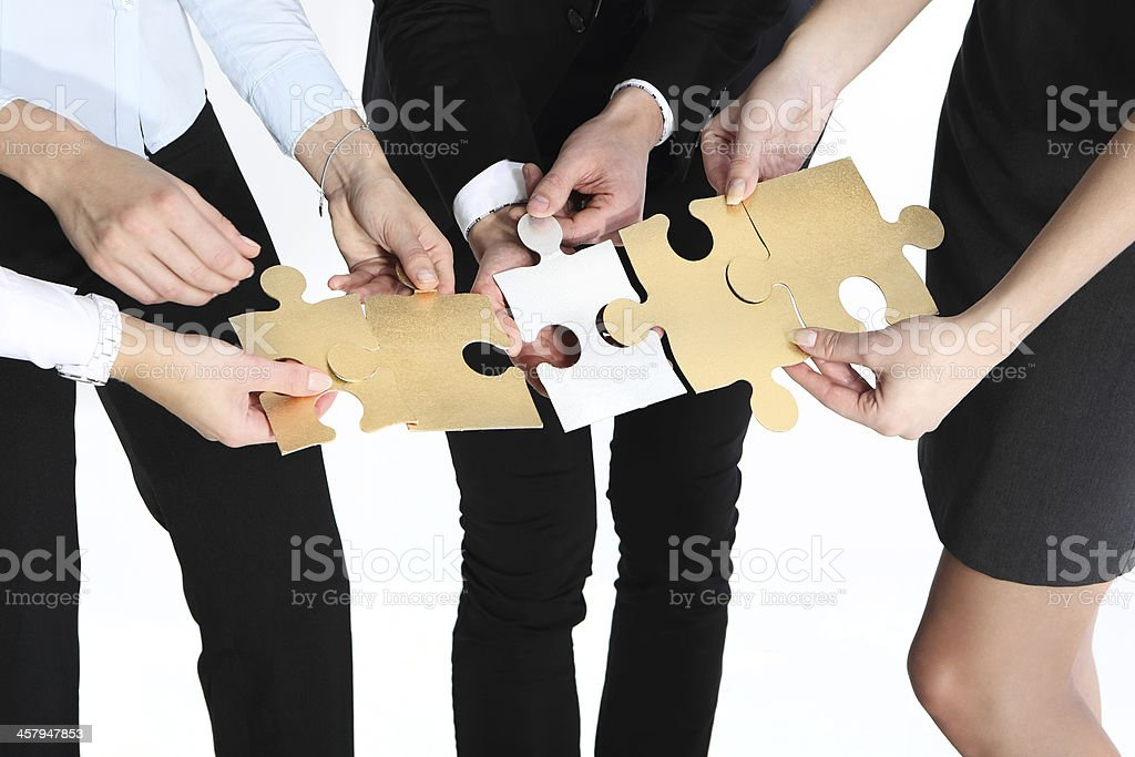 Four sets of hands piecing together gold and white puzzle stock photo